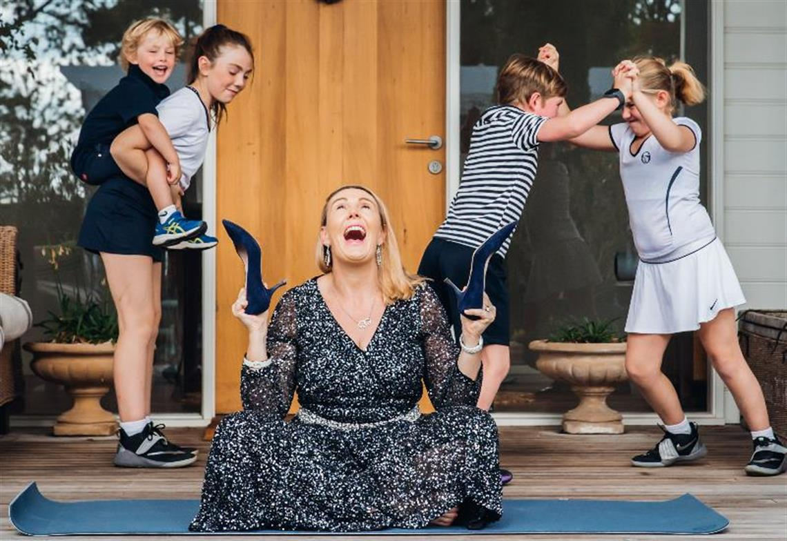 Lisa Atkinson sits on a mat holding shoes with four children behind her Frankston Arts Centre
